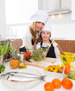 Kid girls junior chef friends hug together in countertop with food at cooking school Royalty Free Stock Photo