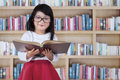 Kid with glasses holds book in library Royalty Free Stock Photo