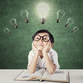 Kid with glasses thinking idea under lamps Royalty Free Stock Photo