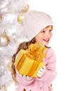 Kid with gold christmas gift box child in hat and mittens holding near white tree isolated Royalty Free Stock Images