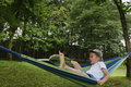 awkward kid on hammock with book away Royalty Free Stock Photo