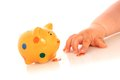 Kid hand and piggybank over white Royalty Free Stock Photo