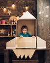 Kid with jet pack. Child playing at home. Success, leader and winner concept. little boy in paper rocket. Royalty Free Stock Photo