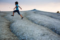 Kid jumping over cracked soil mud volcanoes romania Stock Photo
