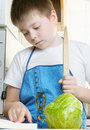 Kid at kitchen with recipe book Stock Photos