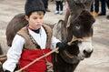 Kid leading donkey