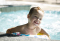 Kid learns to swim using a plastic water ring smiling in the swimming pool or waterpark Royalty Free Stock Photo
