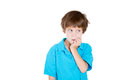 Kid looking sideways biting nails in anxiety closeup portrait of adorable boy blue shirt while fingernails because of craving for Royalty Free Stock Image