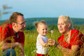 Kid in the meadow blowing dandelion seed parents with and sunshine Royalty Free Stock Image