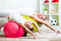 Kid and mother do gymnastic exercises with rubber ball at hom doing home Stock Image
