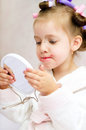 Kid painting lips little girl while wearing hair rollers and bathrobe Stock Photo