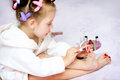 Kid painting nails little girl while wearing hair rollers at home Stock Photos