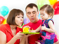 Kid with parents celebrating birthday and blowing candles on ca girl cake Royalty Free Stock Photography