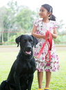 Kid and pet dog cute indian girl with her labrador retriever at outdoor park Stock Image