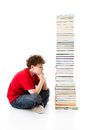 Kid and pile of books young boy sitting next to on white background Royalty Free Stock Photos