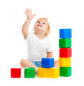 Kid playing with colorful building blocks and looking up on white Stock Photo