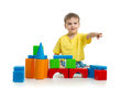 Kid playing with colorful building blocks and pointing direction by finger Royalty Free Stock Photo