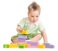 Kid playing colorful toy building blocks in studio Stock Photos