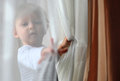 Kid playing with curtains and hiding under Royalty Free Stock Photos