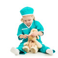 Kid playing doctor and curing toy on white Stock Images