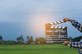 Kid playing film clapper board against summer sky background. Film director concept. Royalty Free Stock Photo