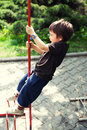 Kid playing outdoors climbing pole Stock Image