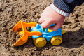 Kid playing in sandbox with toy tractor Royalty Free Stock Photos