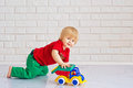 Kid playing with a toy car cute little boy his colorful plastic Royalty Free Stock Photo