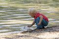 Kid playing by the water. Royalty Free Stock Photography