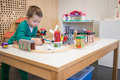 Kid plays with toys toy train at his desk in kindergarden Royalty Free Stock Photography