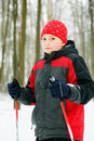 Kid with poles standing in winter forest and looking to camera Royalty Free Stock Photos