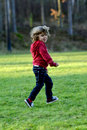 Kid running an jumping playing in autumn sun by the lake Royalty Free Stock Images