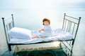 Kid s dream happy child relaxing on vintage bed in sea summer romantic concept Royalty Free Stock Image