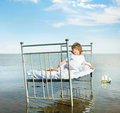 Kid s dreams dreamy child posing on vintage bed on sea shore Royalty Free Stock Photo