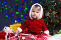 Kid Santa Claus near Christmas tree with gifts Stock Image