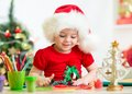 Kid in Santa hat making Christmas decorations from Royalty Free Stock Photo