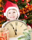 Kid in Santa`s hat holding vintage clock Royalty Free Stock Photos