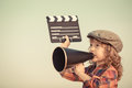 Kid shouting through megaphone holding clapper board and vintage cinema concept retro style Royalty Free Stock Image