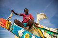 Kid sitting on a colored fisher boat in senegal saint louis december unidentified did with unicef t shirt and blue sky the Stock Photo