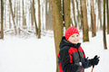 Kid with ski poles standing in winter forest photo the space for copy Royalty Free Stock Images