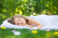 Kid sleeping in spring garden happy on green grass outdoors Royalty Free Stock Photos