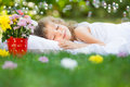 Kid sleeping in spring garden happy on green grass outdoors Royalty Free Stock Photo