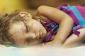 Kid sleeps the face of the little girl which on the bed having taken cover a woollen blanket Royalty Free Stock Image