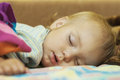 Kid sleeps the face of the little girl which on the bed having taken cover a woollen blanket Stock Photography