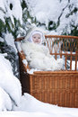 Kid with snowy branch on winewomen bench Royalty Free Stock Photo