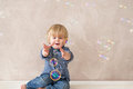 Kid with soap bubbles funny little boy trying to catch colorful Stock Photography