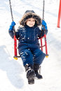 Kid swinging snow sunny winter day Stock Image
