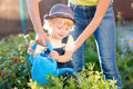 Kid toddler helping mother in the garden sunny summertime Royalty Free Stock Photo