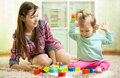 Kid toddler and mothet play wooden toys at home or nursery Royalty Free Stock Photo