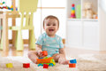 Kid toddler playing wooden toys at home or nursery Royalty Free Stock Photo